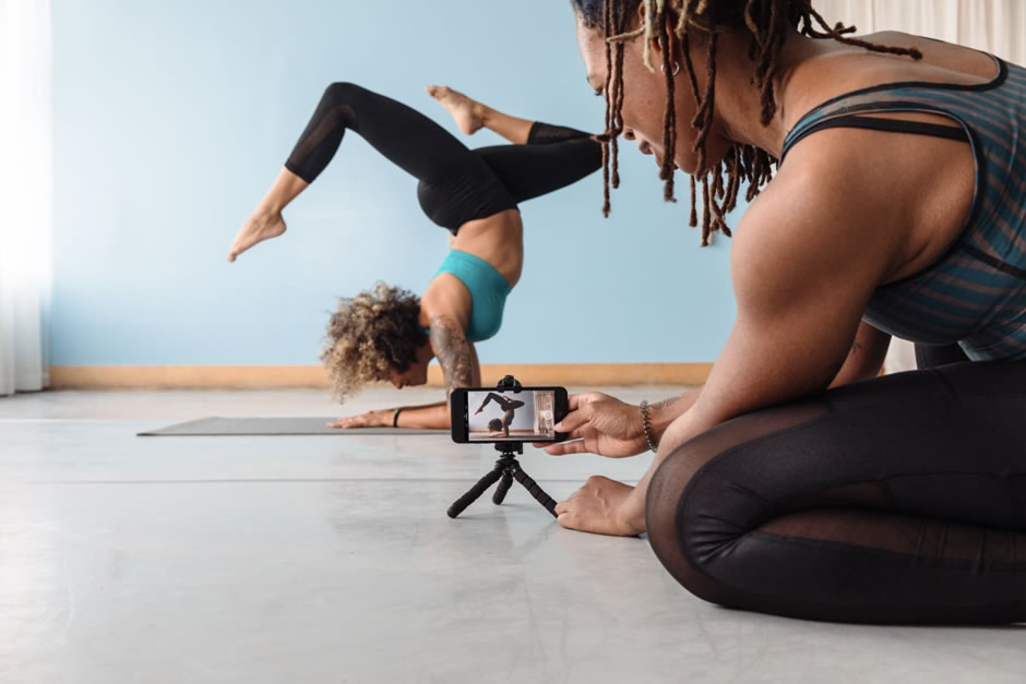 man filming lady doing yoga